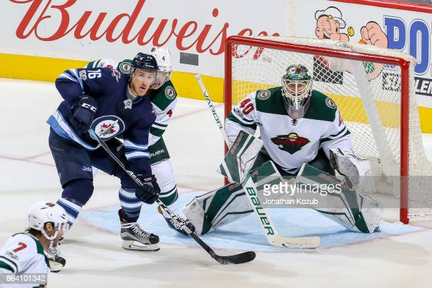 Shawn Matthias of the Winnipeg Jets Mike Reilly and goaltender Devan Dubnyk of the Minnesota Wild keep an eye on the play during second period action...