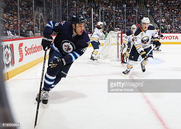 Shawn Matthias of the Winnipeg Jets plays the puck around the boards as Rasmus Ristolainen of the Buffalo Sabres defends during second period action...