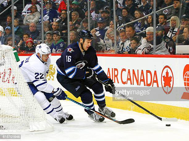 Shawn Matthias of the Winnipeg Jets plays the puck around the net as Nikita Zaitsev of the Toronto Maple Leafs gives chase during first period action...