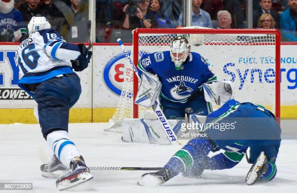 Shawn Matthias of the Winnipeg Jets takes a shot against Jacob Markstrom of the Vancouver Canucks during their NHL game at Rogers Arena October 12...