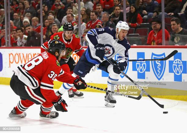 Shawn Matthias of the Winnipeg Jets tries to control the puck under pressure from Jan Rutta and Ryan Hartman of the Chicago Blackhawks at the United...