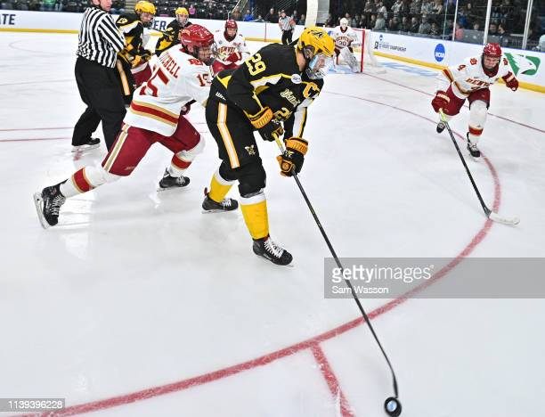 Shawn McBride of the American International Yellow Jackets tries to clear the puck against Ian Mitchell and Griffin Mendel of the Denver Pioneers...
