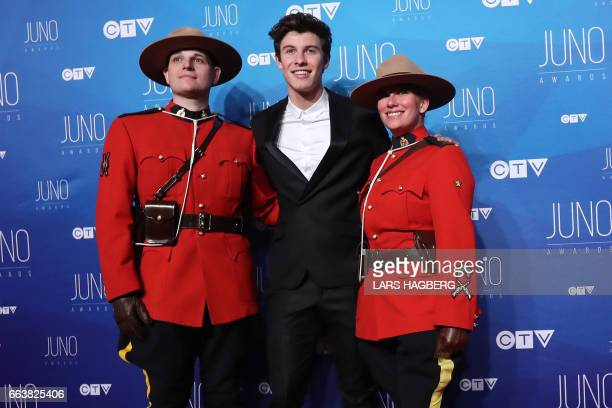 Shawn Mendes poses with RCMP officers as he arrives on the red carpet before the JUNO awards at the Canadian Tire Centre in Ottawa Ontario on April 2...