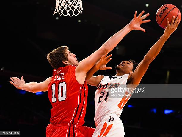 Shawn Olden of the Pepperdine Waves attempts a shot over T.J. Cline of the Richmond Spiders in the second half of the Gotham Classic at Madison...