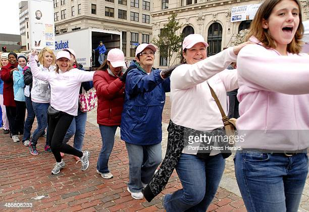 Shawn Patrick Ouellette/Staff Photographer A conga line forms before the walkers set off from Monument Square in Portland for the cancer walk Sunday...