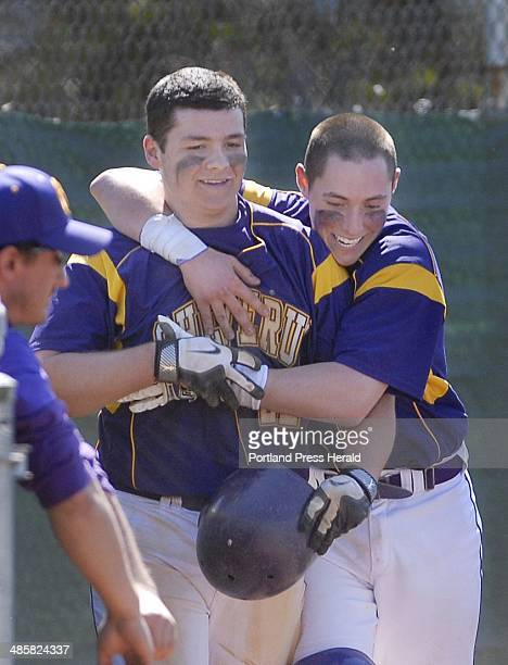 Shawn Patrick Ouellette/Staff Photographer Peter Potthoff of Cheverus left is welcomed by teammate Nic Lops after scoring the winning run on a passed...