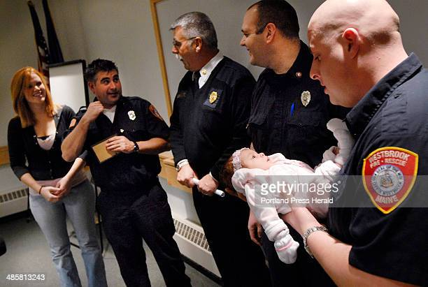Shawn Patrick Ouellette/Staff Photographer -- Westbrook EMT Tony Cataldi, right, holds 3-day-old Aaryhanna Mariah Pettis at the Westbrook Public...