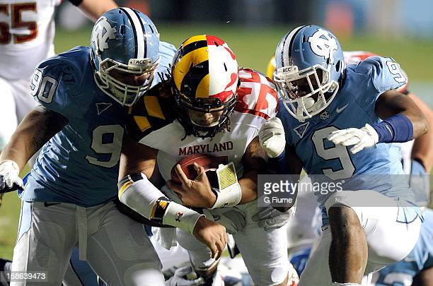Shawn Petty of the Maryland Terrapins is tackled by Jessie Rogers and Travis Hughes of the North Carolina Tar Heels at Kenan Stadium on November 24,...