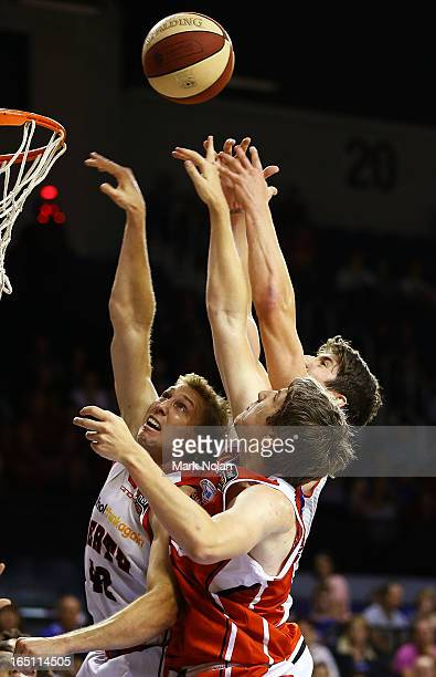 Shawn Redhage and Greg Hire of the Wildcats and Daniel Jackson of the Hawks contest possession during game two of the NBL Semi Final series between...