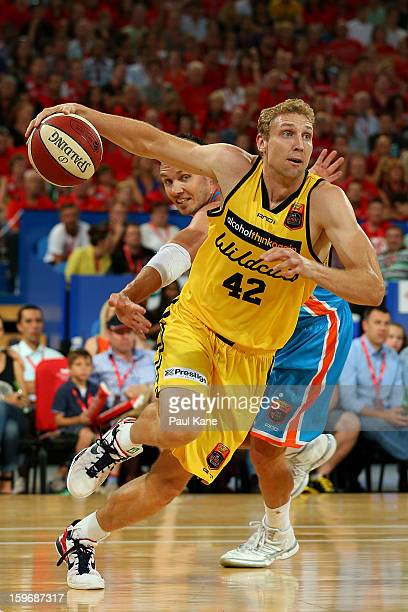 Shawn Redhage of the Wildcats drives past Alex Loughton of the Taipans during the round 15 NBL match between the Perth Wildcats and the Cairns...