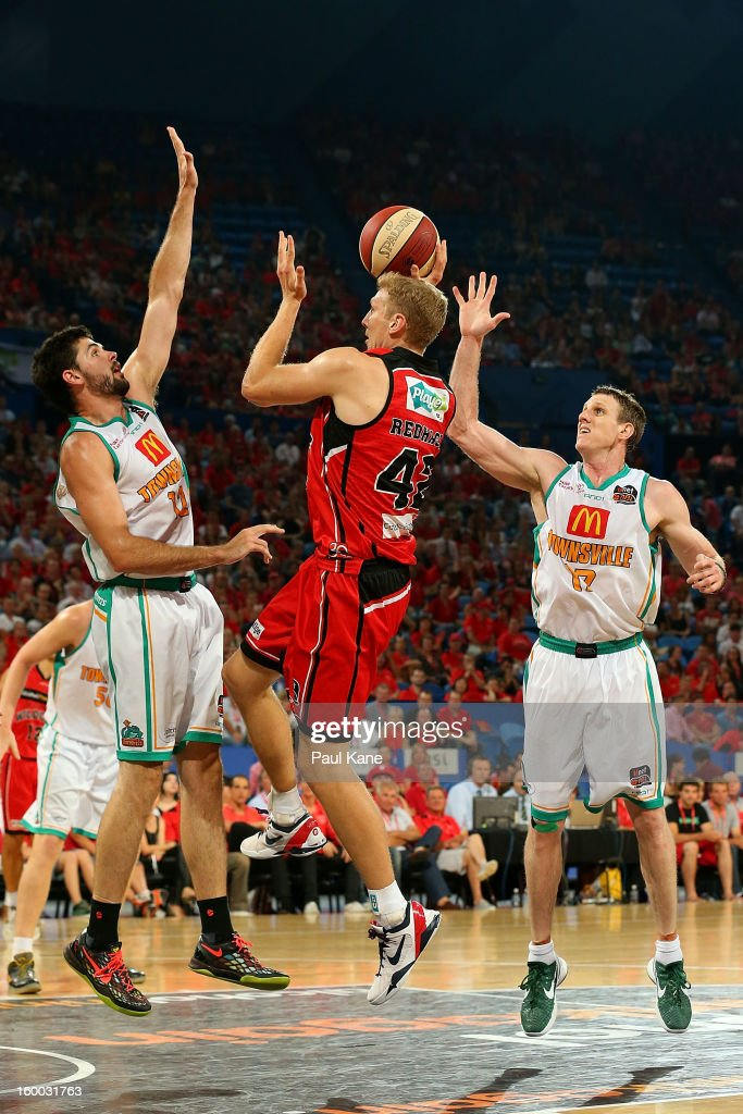 Shawn Redhage of the Wildcats lays up against Todd Blanchfield of the Crocodiles during the round 16 NBL match between the Perth Wildcats and the Townsville Crocodiles at Perth Arena on January 25, 2013 in Perth, Australia.