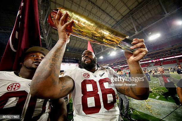 Shawn Robinson of the Alabama Crimson Tide celebrates by hoisting the College Football Playoff National Championship Trophy after defeating the...