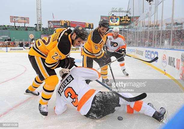 Shawn Thornton and Dennis Wideman of the Boston Bruins watch the loose puck against Oskars Bartulis the Philadelphia Flyers in the 2010 Bridgestone...