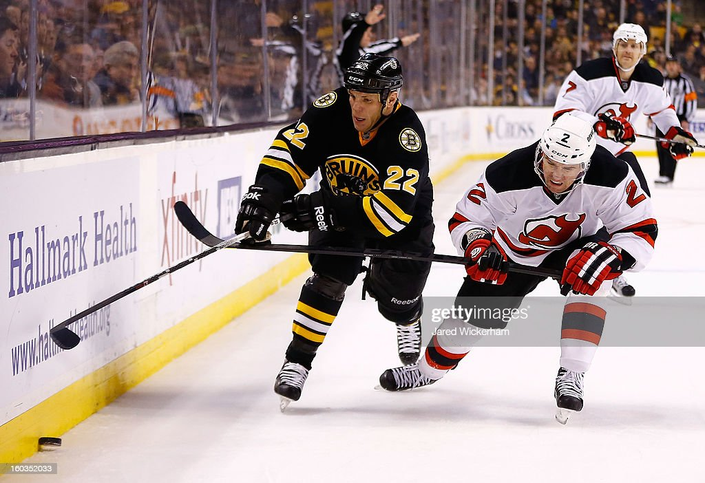 Shawn Thornton #22 of the Boston Bruins attempts to corral the puck along the boards against Marek Zidlicky #2 of the New Jersey Devils during the game on January 29, 2013 at TD Garden in Boston, Massachusetts.