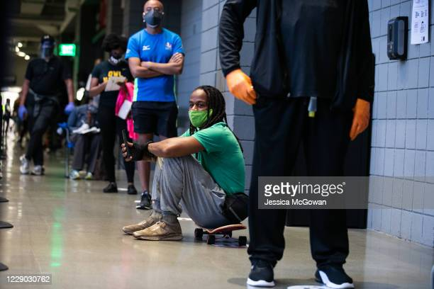 Shawn Walton sits on his skateboard as he waits in line at State Farm Arena, Georgia's largest early voting location, to cast his ballot during the...