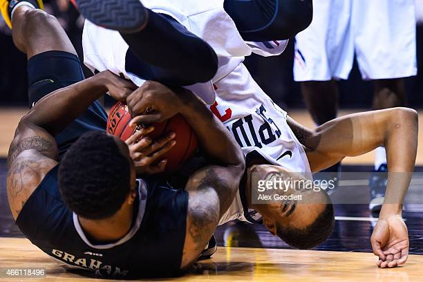 ShawnDre' Jones of the Richmond Spiders fights for the ball with Treveon Graham of the Virginia Commonwealth Rams during a quarterfinal game in the...