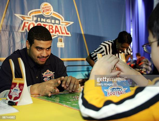 Shawne Merriman of the San Diego Chargers lines up an extra point attempt against a young fan at The BURGER KING Finger Football Challenge at PLAYERS...