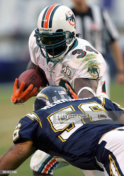 Shawne Merriman of the San Diego Chargers tries to tackle Ricky Williams of the Miami Dolphins during the NFL game on December 11 2005 at Qualcomm...