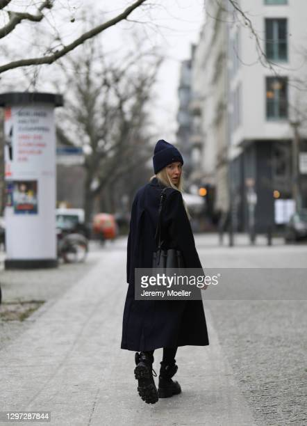 Shawny Sander wearing vintage coat, Filippa K sweater, Acne Studios hat, Polene Paris bag and Prada boots on January 18, 2021 in Berlin, Germany.
