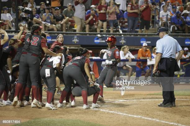 Shay Knighten of the University of Oklahoma meets her teammates at home plate after scoring a run against the University of Florida during the...