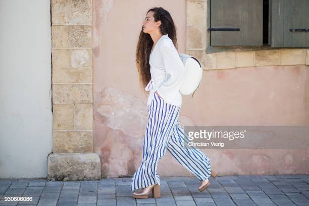 Shaylee Nissim wearing striped pants white blouse white backpack is seen during Tel Aviv Fashion Week on March 11 2018 in Tel Aviv Israel