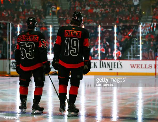 Shayne Gostisbehere and Nolan Patrick of the Philadelphia Flyers stand on the blue line prior to the National Anthem against the Chicago Blackhawks...
