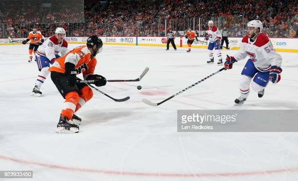 Shayne Gostisbehere of the Philadelphia Flyers battles for the loose puck against Daniel Carr and Victor Mete of the Montreal Canadiens on February...