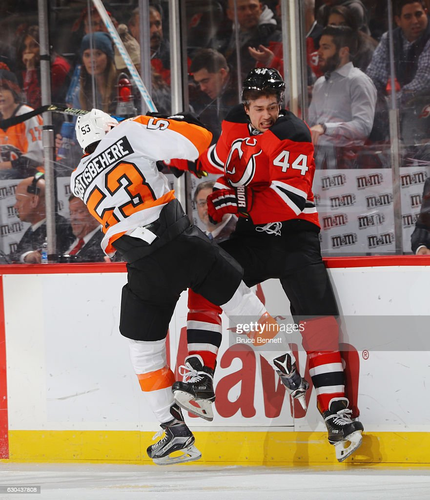 Shayne Gostisbehere #53 of the Philadelphia Flyers checks Miles Wood #44 of the New Jersey Devils into the boards during the second period at the Prudential Center on December 22, 2016 in Newark, New Jersey.