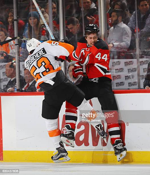 Shayne Gostisbehere of the Philadelphia Flyers checks Miles Wood of the New Jersey Devils into the boards during the second period at the Prudential...