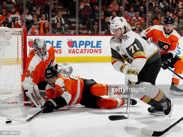 Shayne Gostisbehere of the Philadelphia Flyers knocks away a shot by William Karlsson of the Vegas Golden Knights in the third period as Petr Mrazek...