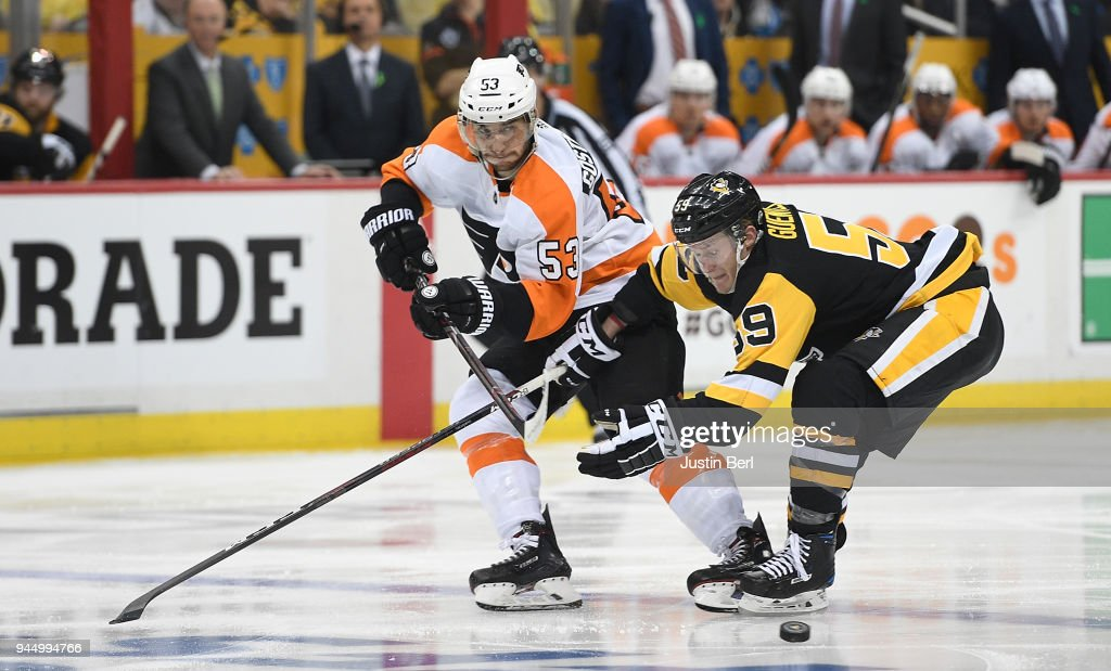 Shayne Gostisbehere #53 of the Philadelphia Flyers makes a pass under pressure from Jake Guentzel #59 of the Pittsburgh Penguins during the third period in Game One of the Eastern Conference First Round during the 2018 NHL Stanley Cup Playoffs at PPG PAINTS Arena on April 11, 2018 in Pittsburgh, Pennsylvania.