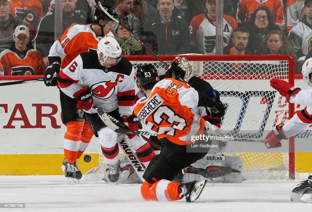 Shayne Gostisbehere #53 of the Philadelphia Flyers shoots the puck wide of goaltender Keith Kinkaid #1 of the New Jersey Devils as Andy Greene #6 defends against Flyer Travis Konecny #11 on February 13, 2018 at the Wells Fargo Center in Philadelphia, Pennsylvania.
