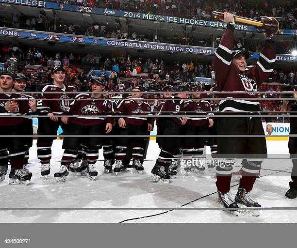Shayne Gostisbehere of the Union College Dutchmen celebrates with the championship trophy after the win over the Minnesota Golden Gophers during the...