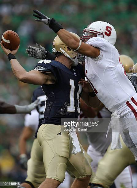 Shayne Skov of the Stanford Cardinal hits Dayne Crist of the Notre Dame Fighting Irish forcing Crist to fumble at Notre Dame Stadium on September 25...