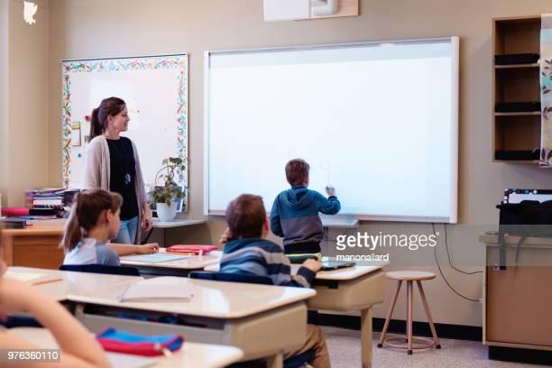 shcoolboy schreiben lektion in interaktiven whiteboards im unterricht - interaktivität stock-fotos und bilder