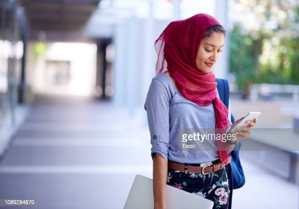 she can check her timetable on her device - middle east stock pictures, royalty-free photos & images