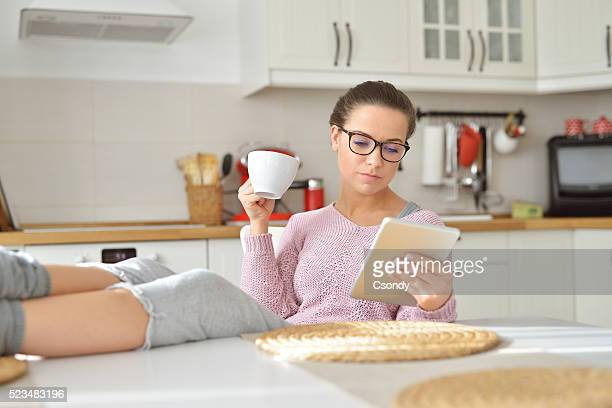 She drinks coffee at home and reading on the tablet