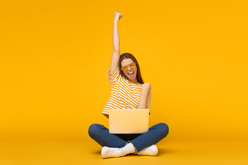 She is a winner! Excited young female with laptop isolated on yellow background 1150254184
