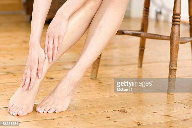 she is maintaining her skin.  - pretty asian feet stock photos and pictures