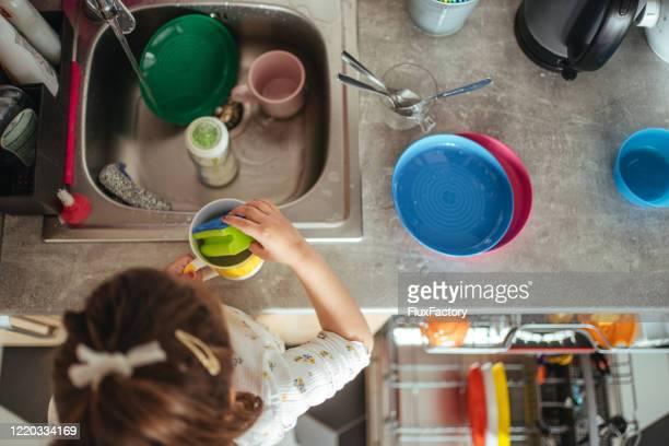 ela está tão focada enquanto lava caneca de café - plastic plate - fotografias e filmes do acervo