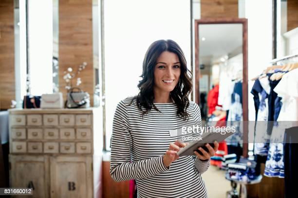 ella está trabajando en línea en una tienda por departamentos - ayudante fotografías e imágenes de stock