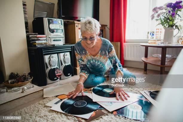 she loves her vinyl records - young at heart woman fotografías e imágenes de stock