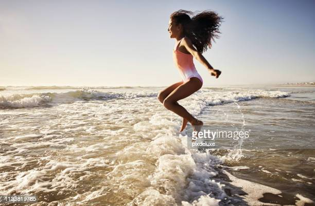 she loves jumping and skipping over all the waves - swimwear stock pictures, royalty-free photos & images