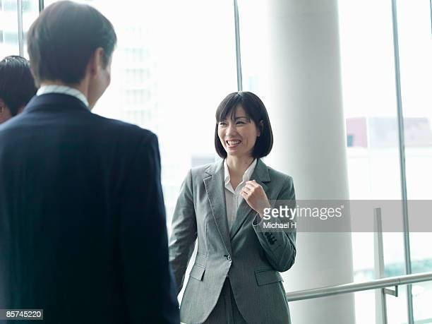 She talks with colleague's businessmen.