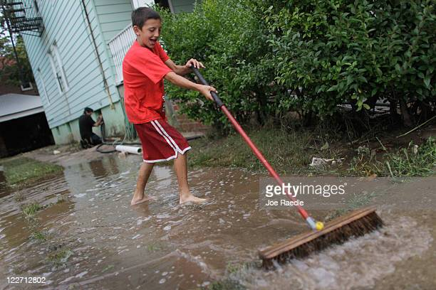 Shea Dolan uses a broom to sweep water into the street as they use a sump pump to remove water from a flooded basement caused when Hurricane Irene...