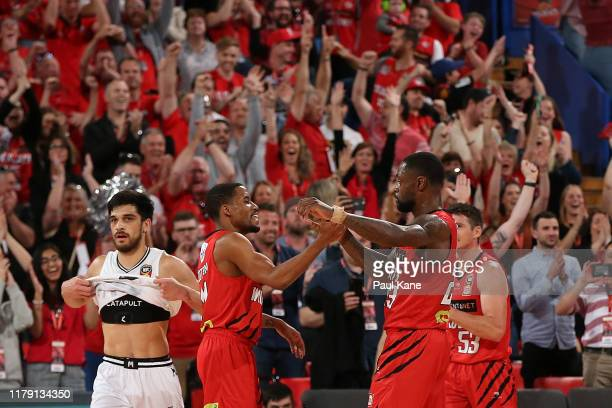 Shea Ili of United looks on as Bryce Cotton and Terrico White of the Wildcats celebrate winning the round one NBL match between the Perth Wildcats...