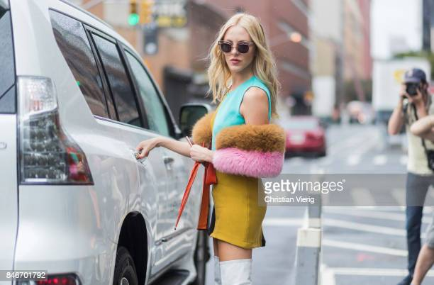 Shea Marie in front of a Lexus wearing yellow skirt white overknee boots seen in the streets of Manhattan outside Marchesa during New York Fashion...