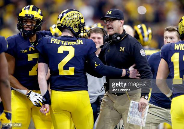 Shea Patterson and head coach Jim Harbaugh of the Michigan Wolverines celebrate the first quarter touchdown against the Florida Gators during the...