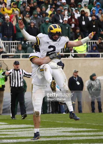 Shea Patterson of the Michigan Wolverines celebrates a second half touchdown with Ben Mason at Spartan Stadium on October 20 2018 in East Lansing...