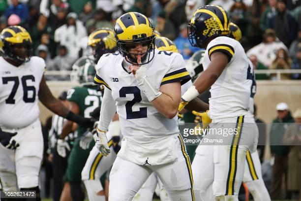 Shea Patterson of the Michigan Wolverines reacts to a teammates second quarter touchdown while playing the Michigan State Spartans at Spartan Stadium...